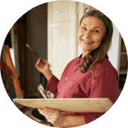 Close up shot of gorgeous cheerful senior woman artist standing in front of easel in her workshop, making picture, painting still life using acrylic paints, looking at camera with happy smile